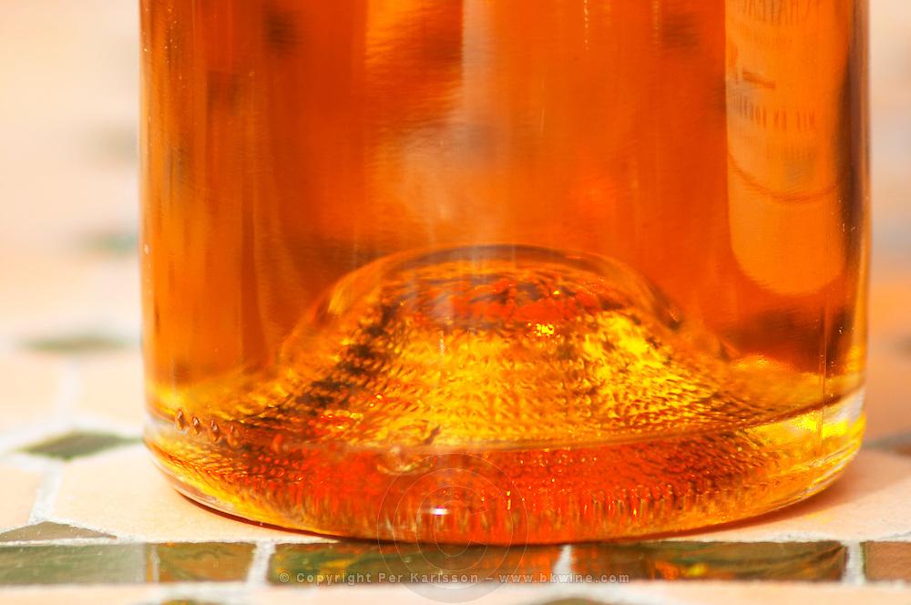 The base of the bottle with golden shining liquid - A bottle of Chateau Mont Redon Vieux Marc de Chateauneuf, eau de vie de marc des cotes du Rhone. Spirit made from chateauneuf wine press residues. The restaurant Le Verger de Papes in Chateauneuf-du-Pape Vaucluse, Provence, France, Europe