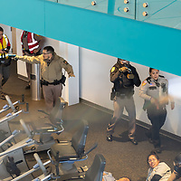 Navajo Nation officers and first response teams look for simulated survivors in the fitness center at the Tséhootsooí Medical Center, as part of the active shooter training exercise, in Window Rock on Thursday.