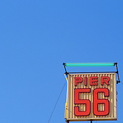 Neon sign for Pier 56 against a clear blue sky