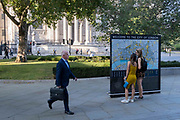 With the pillars and architecture of St Pauls Cathedral in the distance, visitors to London stop to view a detailed map of the City of London, the capitals historic financial district, on 8th September 2021, in London, England.