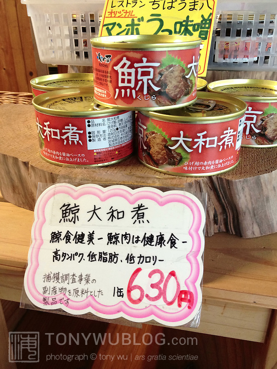Canned whale meat for sale at a souvenir shop for tourists in Japan. The label states that the contents are from an unspecified baleen whale. The sales sign states that whale meat is a food that is good for health and beauty, being high in protein, low in fat, low in calories.