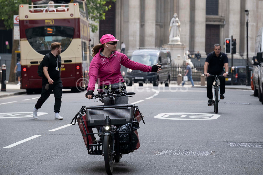 With the statue of Queen Anne and St Pauls Cathedral in the background, a woman delivery cyclist indicates and holds out her hand to make a left turn on Ludgate Hill in the City of London, on 24th June 2021, in London, England.