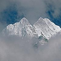 Khumbu Region, Himalaya, Nepal.  6,608-meter Mount Thamserku appears through hole in afternoon clouds.