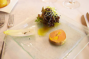 A starter dish: A slice of fresh foie gras duck's liver with salad lettuce, poppy seed sprouts, endive on a glass plate at the restaurant Urbain Dubois in Saint Zacharie, near Bandol, Var, Provence, France
