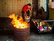 """15 FEBRUARY 2018 - BANGKOK, THAILAND:  A man burns """"ghost money"""" for Tet in front of his home in Bangkok's Chinatown. Lunar New Year, also called Tet or Chinese New Year, is 16 February this year. The coming year will be the Year of the Dog. Thailand has a large Chinese community and Lunar New Year is widely celebrated in Thailand, especially in Bangkok and large cities with significant Chinese communities.    PHOTO BY JACK KURTZ"""