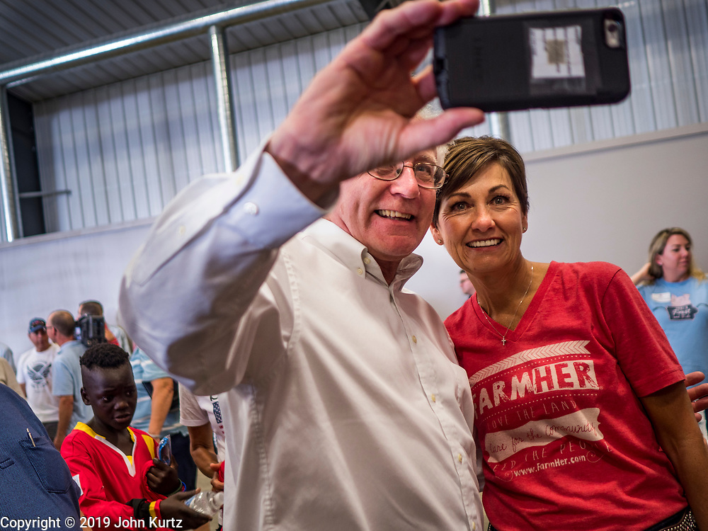 """15 JUNE 2019 - BOONE, IOWA: Governor KIM REYNOLDS (R-IA) poses for a """"selfie"""" at """"Joni's Roast and Ride,"""" an annual fund raiser held by US Senator Joni Ernst (R-IA). Ernst, Iowa's junior US Senator, kicked off her re-election campaign during the """"Roast and Ride"""", an annual fund raiser and campaign event has she held since originally being elected to the US Senate in 2014.  PHOTO BY JACK KURTZ"""