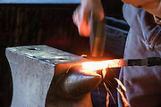 Blacksmith hammer strikes out slag from glowing iron. Conner Prairie Interactive History Park provides family-friendly fun for all ages in Fishers, Indiana, USA. Founded by pharmaceutical executive Eli Lilly in the 1930s, Conner Prairie living history museum now recreates life in Indiana in the 1800s on the White River and preserves the William Conner home (listed on the National Register of Historic Places).