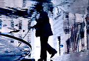 Reflection in puddle of man walking with cane