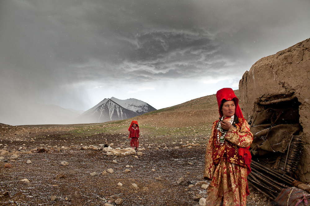 It is late June and two of the Khan's daughter's venture outside their mud hut after a hailstorm at the family's autumn camp beside the Aksu river. The nomads sometimes stop here for a few weeks between migratory seasons if grass for their herds is too scarce at the summer or winter camps...