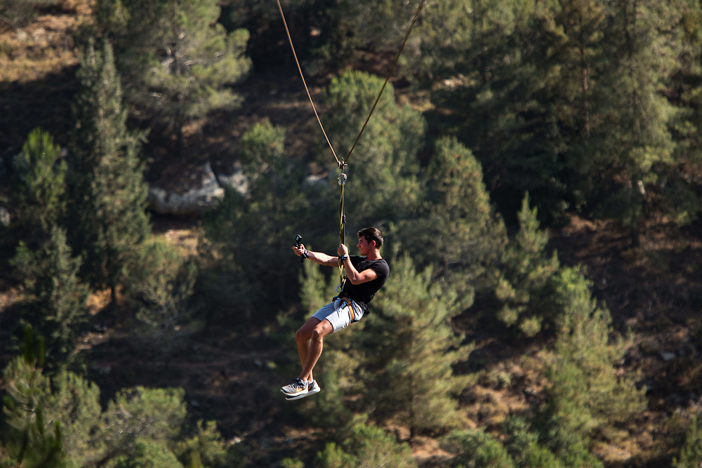 A man takes a selfie as he rides a zipline that runs 400 meters at an altitude of 120 meters over a valley at Deer Land Farm (Eretz HaAyalim), near the West Bank Jewish settlement of Alon Shvut in the Gush Etzion settlement bloc, southwest of the Palestinian city of Bethlehem, on June 8, 2017.