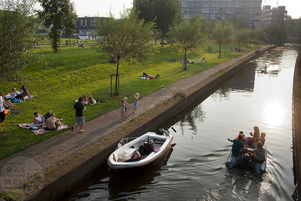 Mensen genieten in en rond het water op de eerste dag van oktober in het Griftpark van zomers weer.<br /> <br /> People are enjoying themselves on a summerly day in October at the Griftpark in Utrecht.
