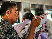 26 OCTOBER 2015 - YANGON, MYANMAR: A man reads a newspaper on the Yangon Circular Train. The Yangon Circular Railway is the local commuter rail network that serves the Yangon metropolitan area. Operated by Myanmar Railways, the 45.9-kilometre (28.5mi) 39-station loop system connects satellite towns and suburban areas to the city. The railway has about 200 coaches, runs 20 times daily and sells 100,000 to 150,000 tickets daily. The loop, which takes about three hours to complete, is a popular for tourists to see a cross section of life in Yangon. The trains run from 3:45 am to 10:15 pm daily. The cost of a ticket for a distance of 15 miles is ten kyats (~nine US cents), and for over 15 miles is twenty kyats (~18 US cents).    PHOTO BY JACK KURTZ