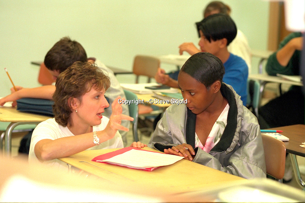 Teacher helping student ages 35 and 16 during class.  New Hope Minnesota USA