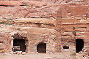 A pickup truck is parked inside a carved Nabatean cave in Petra, Jordan.