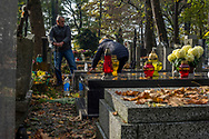 A couple is cleaning a gravestone in Rakowicki cemetery in Krakow, Poland 2019.