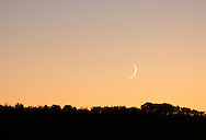 Scotchtown, New York - The crescent moon sets over a ridge as seen from Highland Lakes State Park on Oct. 9, 2010.