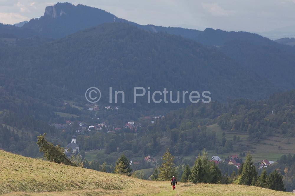 A single hiker descends from the tops of southern Polish mountains, on 20th September 2019, Biala Woda, Jaworki, near Szczawnica, Malopolska, Poland.