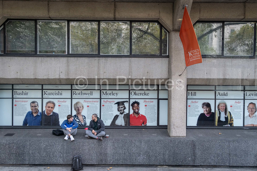 Two young men talk on a wall near the faces of past alumni a wall outside King's College London University on the Strand, during the second wave of the Coronavirus pandemic, and when the capital is designated by the government as a Tier 2 restriction, on 20th October 2020, in London, England.