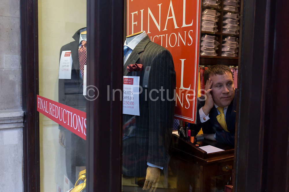 A bored-looking shop assistant in the window of a City gents outfitters, on 9th February 2017, in the City of London, England. Traditional City bowler hats and pinstripe suits are now rare, even among older bankers and financiers.