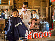 27 FEBRUARY 2015 - PONHEA LEU, KANDAL, CAMBODIA: A barber cuts a boy hair in his shop in rural Cambodia.    PHOTO BY JACK KURTZ