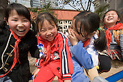 Children giggling in the playground of a primary school in Hong Ying Road, Xian. China has a one child policy to limit population.