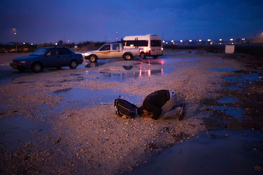 A Palestinian man is praying in the parking lot of the Eyal crossing point , near the Israeli city of Kfar-Saba<br /> Each day Palestinian workers pass through cross points like this one in order to work in Israel.