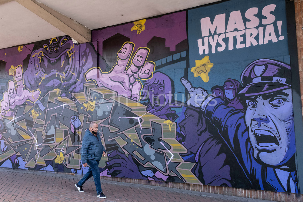 Mass hysteria street art graffiti mural in the Chinese Quarter as the third national coronavirus lockdown in Birmingham continues, the city centre is empty and quiet as the country awaits the easing of lockdown restrictions on 24th March 2021 in Birmingham, United Kingdom. Following the recent surge in cases including the new variant of Covid-19, this nationwide lockdown, which is an effective Tier Five, came into operation yesterday, with all citizens to follow the message to stay at home, protect the NHS and save lives.
