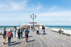 Visitors walking along Cromer Pier in Norfolk.