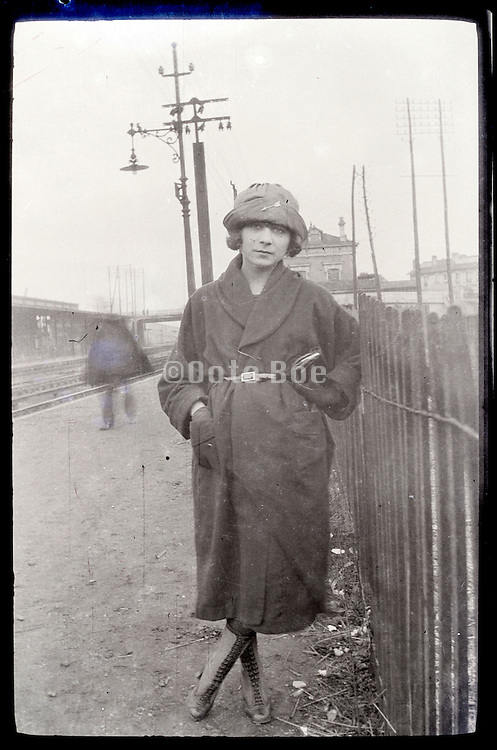 young adult woman standing by fence 1900s