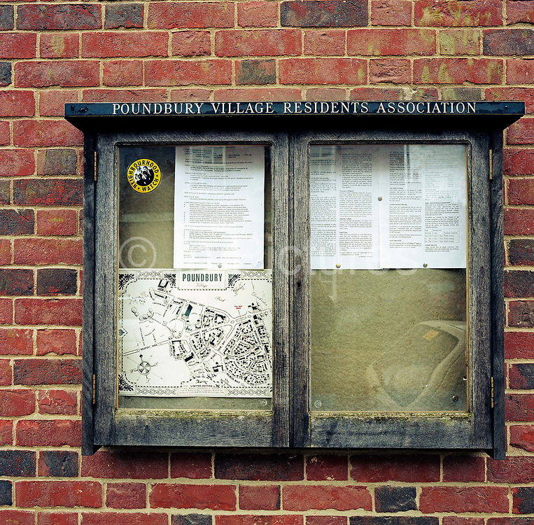 Showing a Neighbourhood Watch sticker to discourage crime, a map and various by-laws, the Resident's Association Information Board is attached to a brick wall on Middlemarsh Street in the experimental community village of Poundbury, Dorset, England. The wooden case needs treating and the glass needs wiping but there is a feeling of security and of a close and friendly community. Poundbury is the visionary model village that Charles, Prince of Wales sought to develop in 1993 as a successful and pioneering town near Dorchester, built on land owned by his own Duchy of Cornwall, challenging otherwise poor post-war trends in town planning and to some extent following the New Urbanism concept from the US except that the design influences are European.