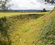 Deep defensive ditch and rampart at Old Sarum castle, Salisbury, Wiltshire, England, UK