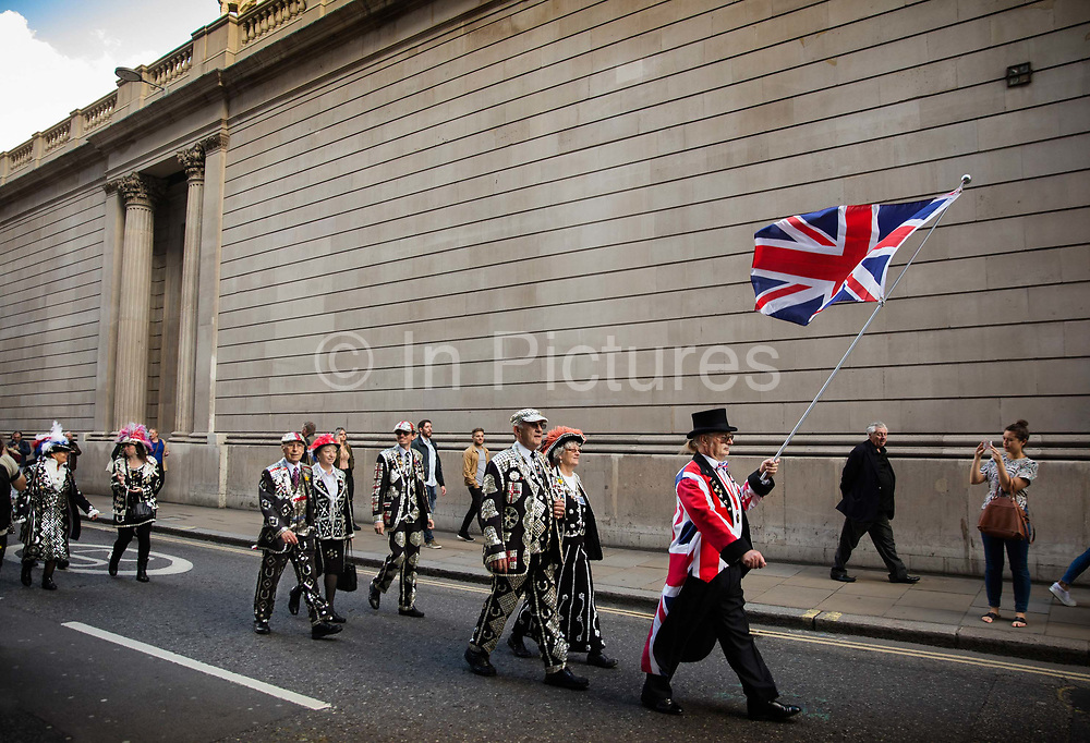 Pearly Kings and Queens parade around the City of London to St Mary-le-Bow Church for the annual Harvest Festival celebrations. The Chelsea pensioners & all the mayors of London take part in this traditional London event.<br /> The London tradition of the Pearly Kings and Queens began in 1875, by Henry Croft. Inspired by the local Costermongers, a close-knit group of market traders who looked after one another and were recognisable by buttons sewed onto their garments, Henry went out on the streets to collect money for charity, wearing a suit covered in pearl buttons to attract attention. When demand for his help became too much, Henry asked the Costermongers for assistance, many of whom became the first Pearly Families. Today, around 30 Pearly Families continue the tradition to raise money for various charities.