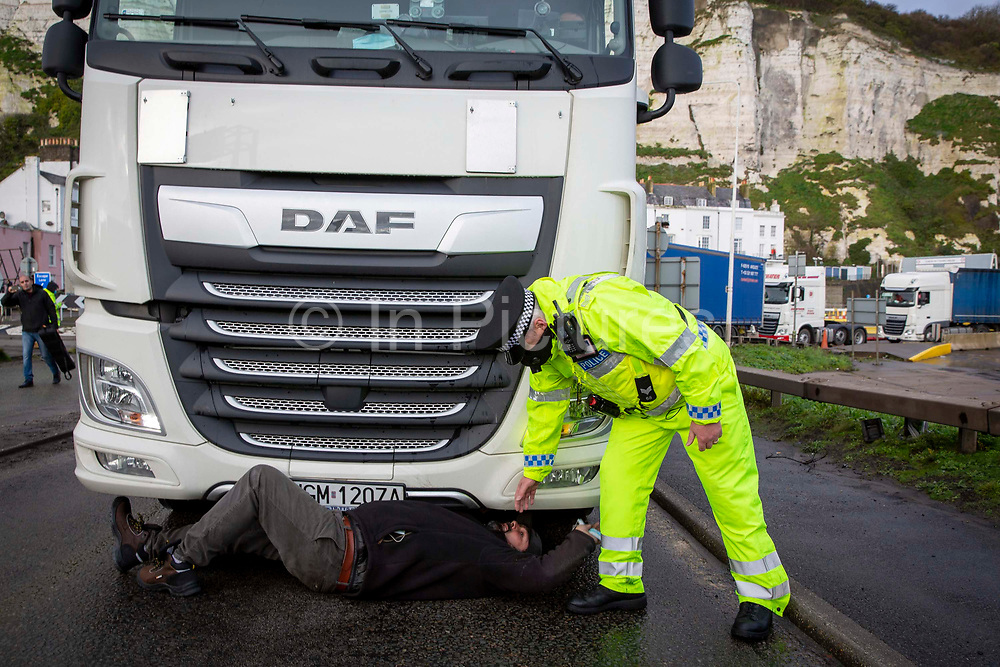 A truck driver tries to blockade a lorry leaving the port as tensions are high between police and drivers who have been waiting over 48 hours for the Port of Dover to re-open, on the 23rd of December 2020, Dover, Kent, United Kingdom. The French border was closed due to a new strain of COVID-19 all travellers are now waiting to receive a COVID-19 test before they can board a ferry to Calais, France. Dover is the nearest port to France with just 34 kilometres 21 miles between them. It is one of the busiest ports in the world. As well as freight container ships it is also the main port for P&O and DFDS Seaways ferries.