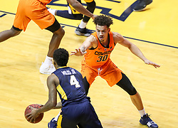 Feb 10, 2018; Morgantown, WV, USA; Oklahoma State Cowboys guard Jeffrey Carroll (30) defends West Virginia Mountaineers guard Daxter Miles Jr. (4) during the first half at WVU Coliseum. Mandatory Credit: Ben Queen-USA TODAY Sports