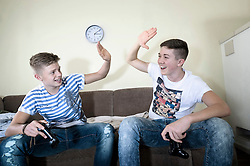 Two teenage boys with video game controllers high fiving