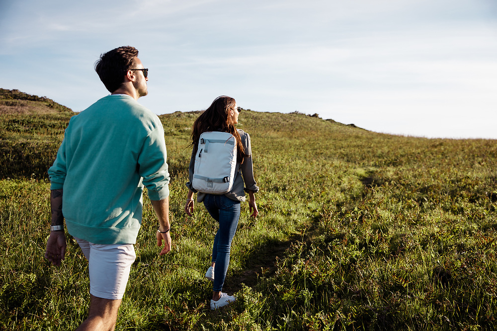 Man and woman walking through the green countryside on the north coast of Jersey, Channel Islands on a sunny day in Spring