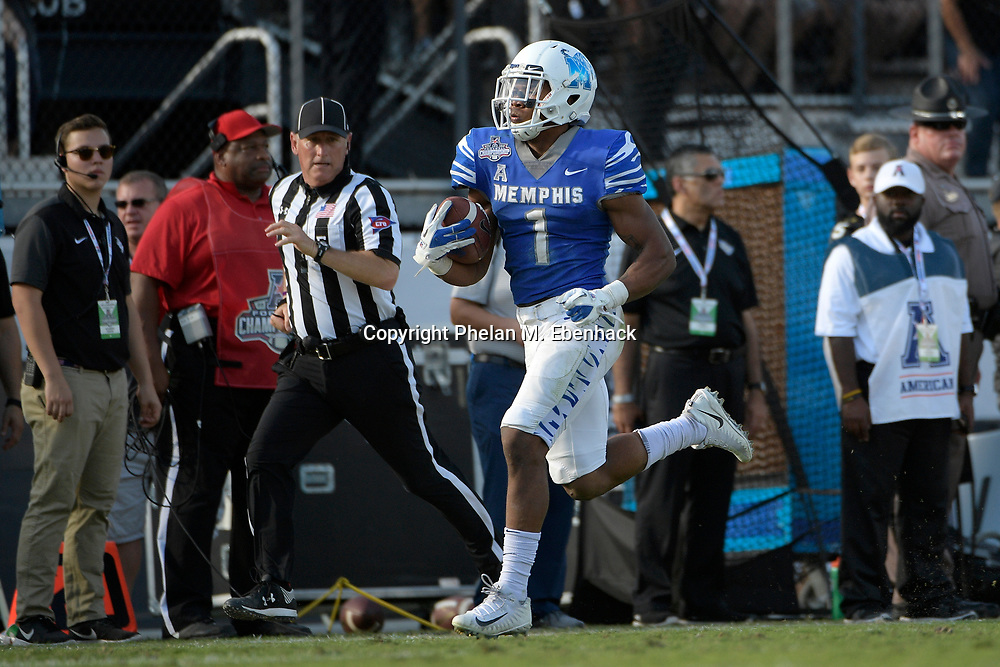 Memphis running back Tony Pollard (1) rushes for a 66-yard touchdown after breaking a tackle attempt by Central Florida defensive back Tre Neal during the second half of the American Athletic Conference championship NCAA college football game Saturday, Dec. 2, 2017, in Orlando, Fla. Central Florida won 62-55. (Photo by Phelan M. Ebenhack)