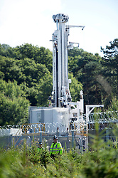 © London News Pictures. 19/08/2013. Balcombe, UK. A police officer stands guard in front of the drill at the Cuadrilla drilling site in Balcombe, West Sussex on a day of of civil disobedience organised by campaign group No Dash For Gas. Cuadrilla has temporarily ceased drilling at the site, which has been earmarked for fracking, under advice from the police. Photo credit: Ben Cawthra/LNP