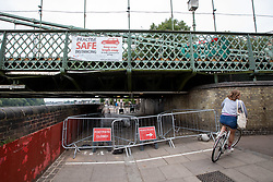© Licensed to London News Pictures. 14/08/2020. London, UK. A cyclist goes around Hammersmith Bridge which crosses the River Thames in West London after Fulham Council suddenly closed it to all traffic Thursday night due to safety concerns. Hammersmith Bridge has been close to all traffic including pedestrians, cyclists and boats going under it after cracks in the bridge have become larger by the heatwave. Photo credit: Alex Lentati/LNP