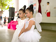 Two young Laotian girls wearing white ballet dresses before their dance performance at the Women's International Group (WIG) bazaar, Vientiane, Lao PDR. The WIG Bazaar is a charity event aiming to raise funds for projects benefitting Lao women and children.