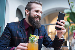 Young man using mobile phone and holding mocktail jar while sitting at restaurant