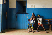 A woman speaks on the phone as she waits with her child at the Libreville health center in Man, Cote d'Ivoire on Wednesday July 24, 2013.