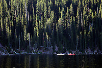 Canoers paddle the calm waters of Shoshone Lake on a recent sunny summer morning. The lake is best navigated early in the day, before afternoon winds kick up waves and whitecaps.