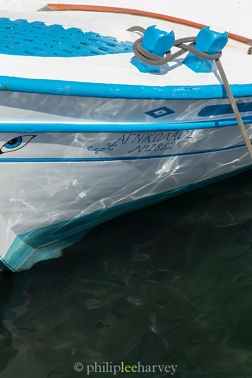 Detail of white and blue boat moored on calm clean waters, Lesbos, Greece