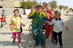 Local children in the Alfar Ahidi area of Basrah rush forwards as Members of Alma Company 1st Batalion The Duke Of Wellingtons Regiment stop at a local Police Station<br />5 March 2005