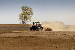 Farm tractor pulling a disc through a field to prepare it for traditional till type planting.