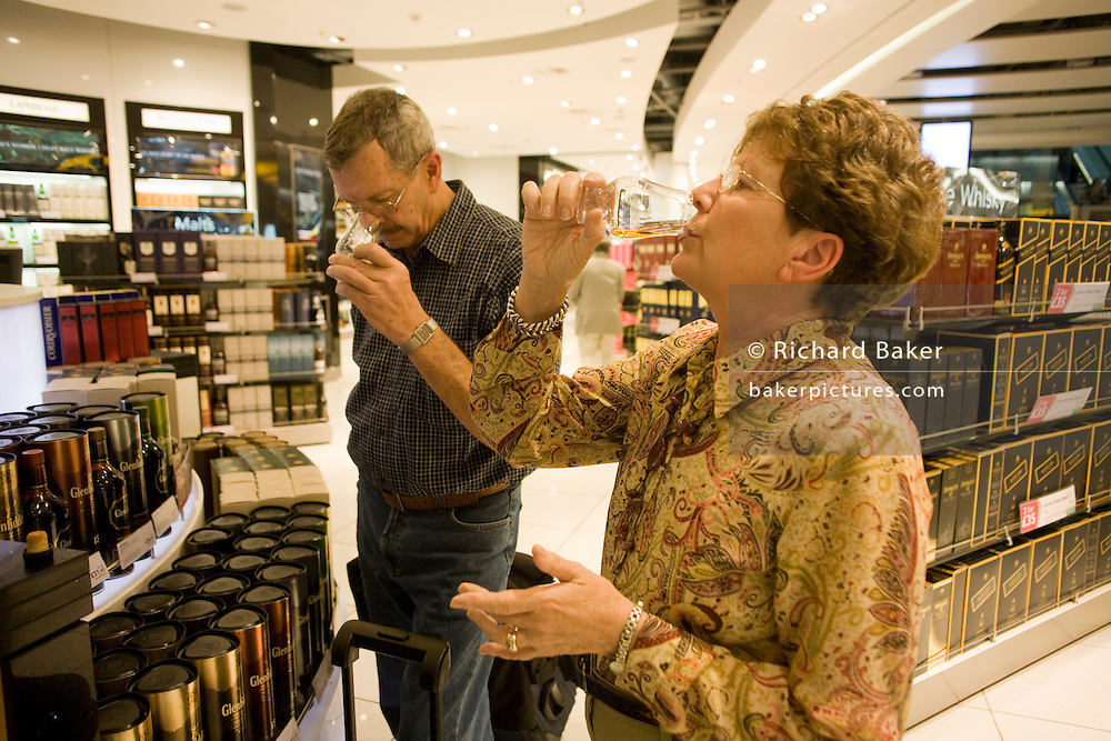 Two elderly passengers taste Scottish Malt Whiskey in a retail space called World of Duty Free in Heathrow airport's terminal 5