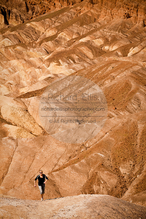 Hiker at the badlands at Zabriskie Point looking toward Golden Canyon in Death Valley National Park, Nevada, USA. Zabriskie point was once the home of twenty-mule team borax mines.