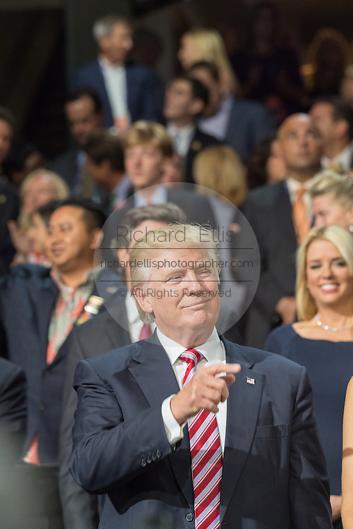 GOP Presidential nominee Donald Trump gestures after arriving at the VIP box during the third day of the Republican National Convention July 20, 2016 in Cleveland, Ohio.