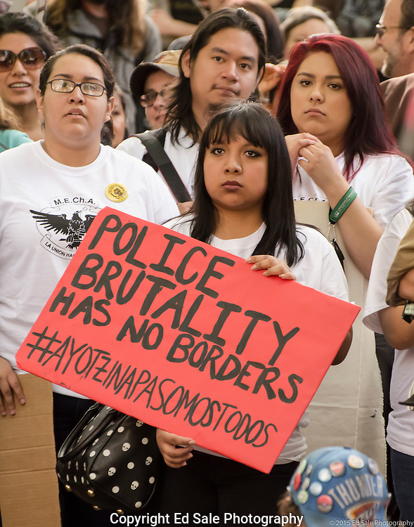 Young Hispanics holding sign that says Police Brutality Has No Borders during 2015 May Day Rally in Portland, Oregon.